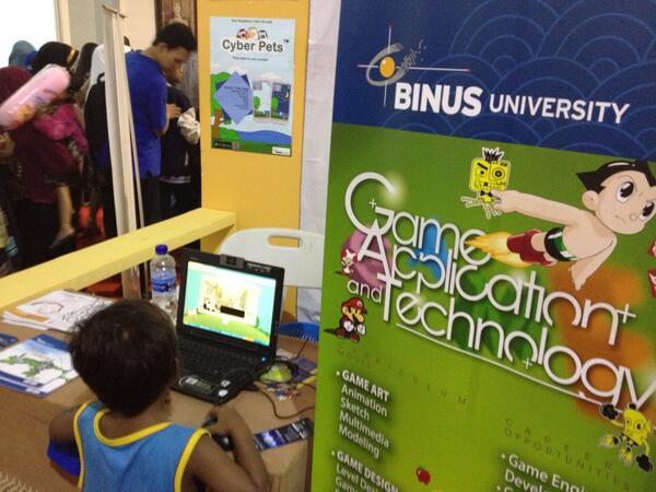 Seorang adik kecil sedang bermain aplikasi game Garuda Kids di stand SoCS